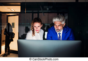Two business people in an office at night., working.