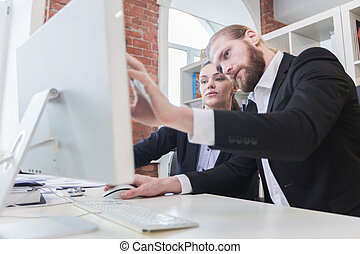 Two business people looking at monitor