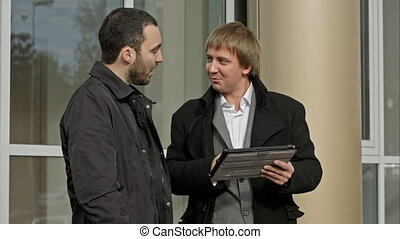 Two business people outdoor with tablet