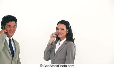 Two business people posing with headsets