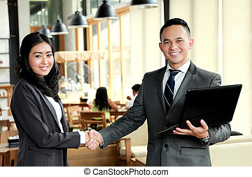 two business people shake hands after have a deal with their project