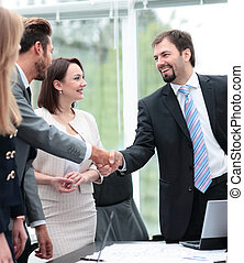 Two business people shaking hands and looking at each other...