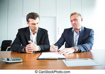 Two business people signing a document