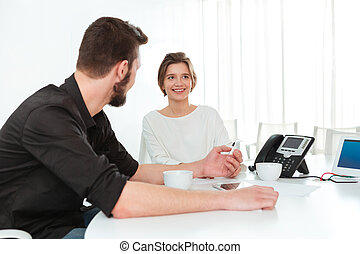 Two business people sitting and talking in office - Two...