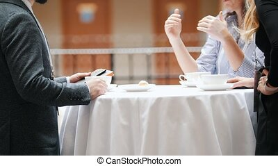 Two business people sitting by the table in buffet and talking while drinking coffee. Mid shot