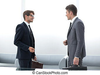 two business people talking standing in the office