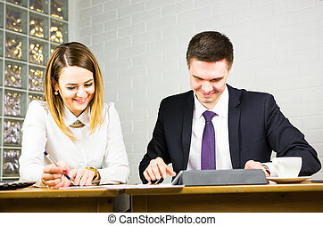 Two business people using tablet computer in office