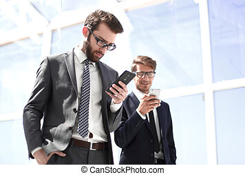 two business people with smartphones