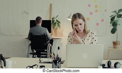 Two business people with wheelchair in the office. - Two...