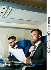 Two Business People Working in Airplane