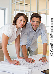 Two business people working on blueprints at office