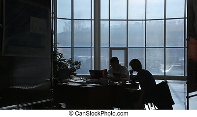 Two business persons work in dark office in evening