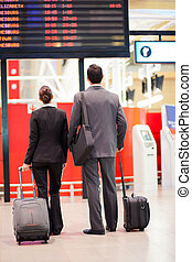 business travelers looking at airport information board