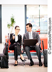 two business travelers waiting for flight at airport