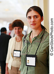 Two business women at trade show with name badges.