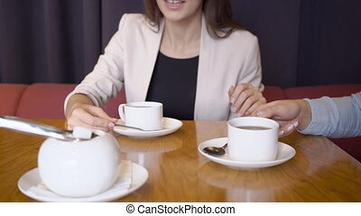 Two business women drink from white cups drink with sugar....