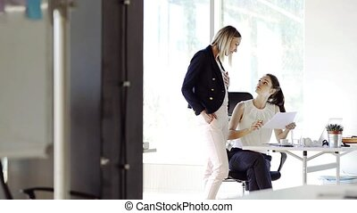 Two business women in the office working together. - Two...