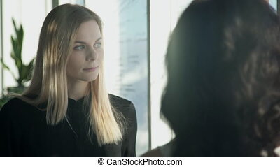 Two business women next to window in hall discuss topics