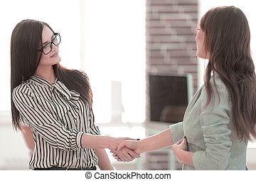 two business women shaking hands.