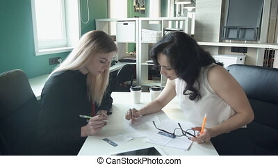 Two business women sitting at table in office discuss topics. tall blonde woman with straight hair, black shirt sits with paper, pen, listening to employee, says, looking at documents. Discussion of operational issues at meeting indoors, Making great decisions, team job. Female with black curly hair...