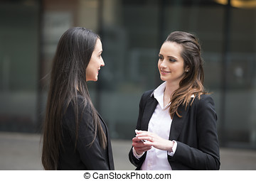 Two business women standing outside talking.