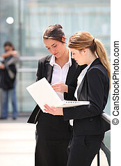 Two business women stood outdoors with laptop computer