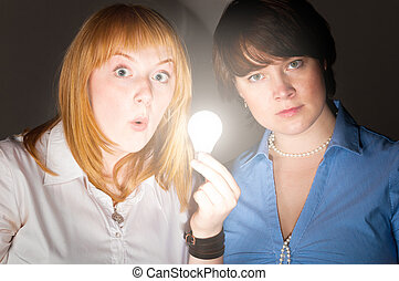 two business women with bulb