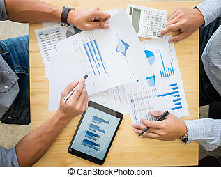 Two businessman calculating Tax Invoice, new project business strategy plan graph and using calculator on Wooden Desk, Coworker process