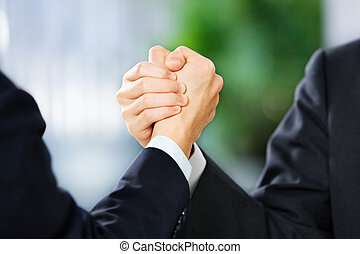 Two businessman grasp each other hand