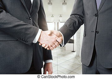Two businessman shaking hands in a light modern office