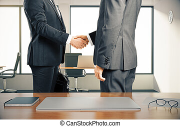 Two businessman shaking hands in a modern office