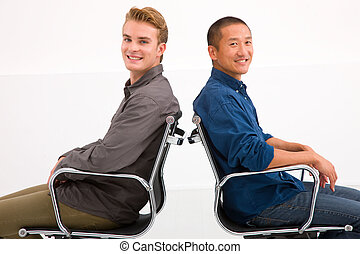 Two businessman sitting in chairs to back