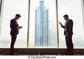 Two businessman using smart phone - Side vie of two ...