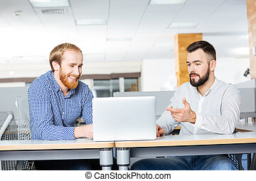 Two businessman working with laptop in office together