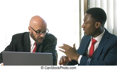 Two businessmen actively gesturing and discussing an important project at a meeting