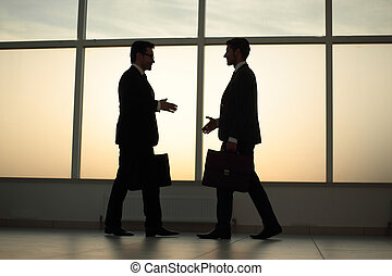 two businessmen are walking towards each other