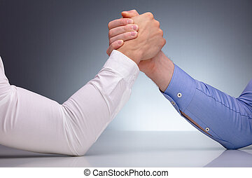 Two Businessmen Arm Wrestling - Close-up Of Two Businessmen...