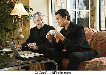 Two businessmen at hotel. - Prime adult Asian and Caucasian...