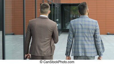 Two businessmen chat together as they walk along through a busy modern office building. Rear view