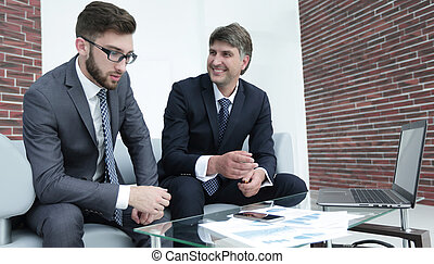 Two businessmen discuss financial documents
