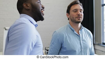 Two Businessmen Discuss Window View In Modern Coworking Space, Mix Race Business People Talking
