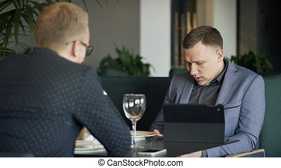Two businessmen discussing business issues with tablet during lunch.