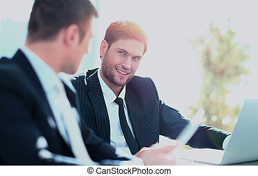 Two businessmen discussing tasks sitting at office table.