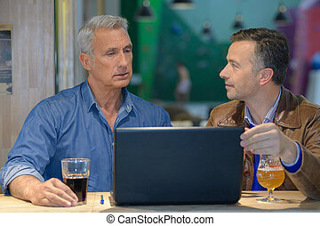 two businessmen drinking beer and working on laptop