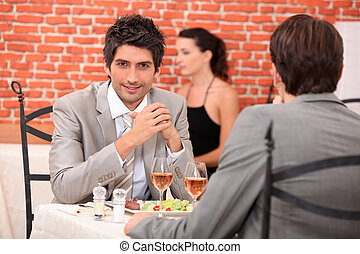 two businessmen eating in a restaurant