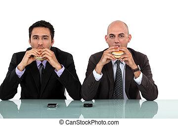 Two businessmen enjoying a burger.