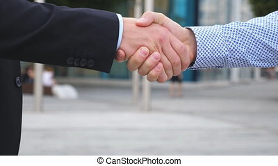 Two businessmen greeting each other in urban environment. Business handshake outdoor. Shaking of male arms outside. Colleagues meet and shake hands in the city background. Close up Slow motion