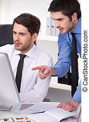 two businessmen having discussion in office. closeup on two businessmen looking at screen with graphs on table