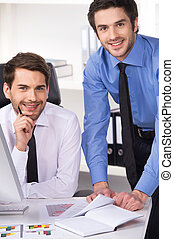 two businessmen having discussion in office. Two businessmen looking at camera and graphs on table