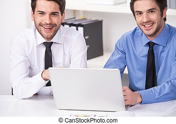 two businessmen having discussion in office. two smiling businessmen looking at camera with laptop
